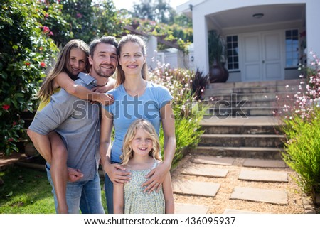 Portrait of family standing together on garden path - stock photo