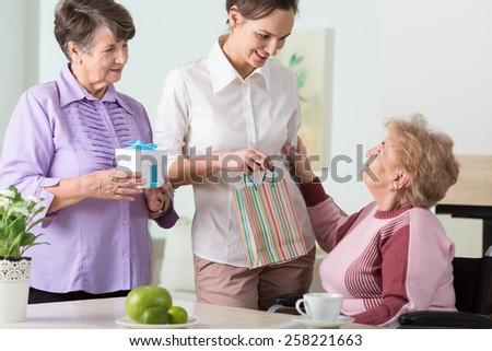 Portrait of family visiting senior woman having birthday - stock photo