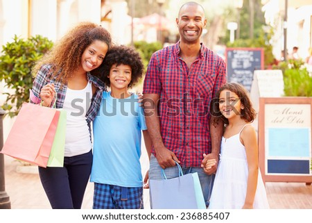 Portrait Of Family Walking Along Street With Shopping Bags - stock photo