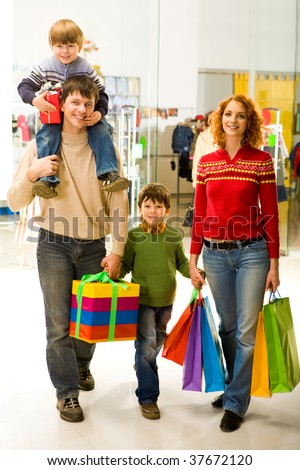 Portrait of family walking down shopping mall after buying Christmas presents - stock photo