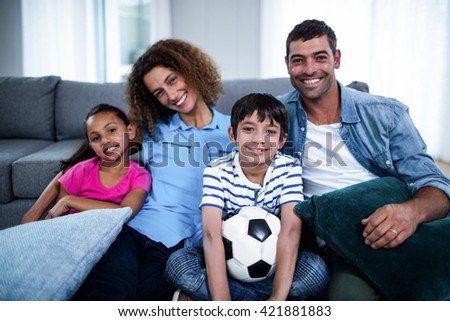 Portrait of family watching match on television at home - stock photo