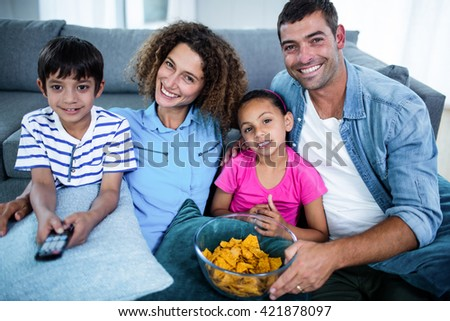 Portrait of family watching match together in living room - stock photo