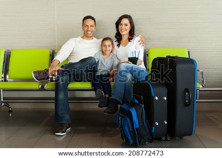 portrait of family with luggage waiting at airport - stock photo