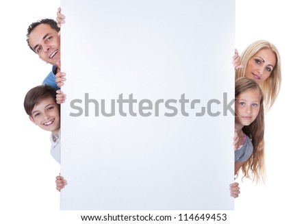Portrait Of Family With Two Children Peeping Behind Blank Board On White Background - stock photo
