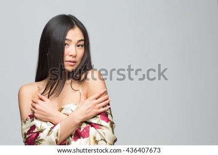 Portrait of fashion asian lady posing in spring or summer dress in studio. Beautiful woman with black hair demonstrating her gorgeous shoulders. - stock photo