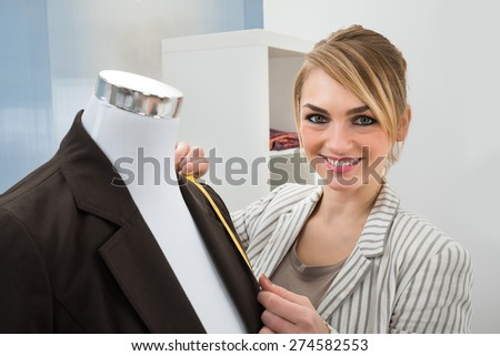 Portrait Of Fashion Designer Measuring Suit With Measuring Tape - stock photo