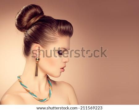 Portrait of fashion girl with professional make-up and retro hairdo. Young beautiful stylish female model wearing luxury jewelery.   - stock photo