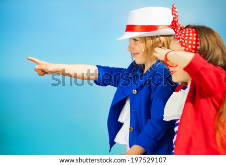 Portrait of fashion kids points to the sea. Vacation, friendship, fashionable concept - stock photo