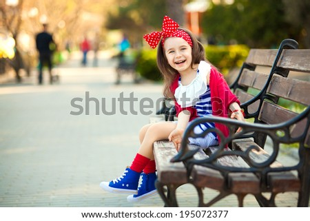 Portrait of fashion little girl in a park, leisure the nature. Close-up. Happiness, fashionable concept. - stock photo