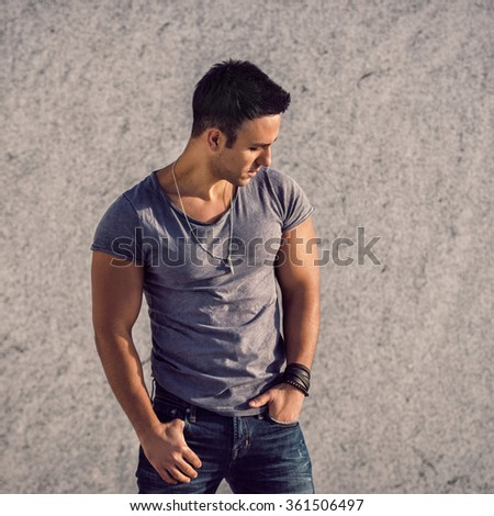 Portrait of fashion model man wearing grey t-shirt and jeans posing in front of the wall - stock photo