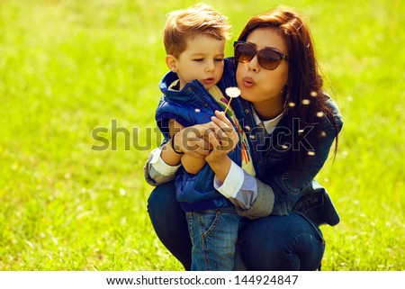 Portrait of fashionable baby boy and his gorgeous mother in trendy sunglasses playing with dandelion in the park. Sunny spring day. Hipster style. Copy-space. Outdoor shot - stock photo