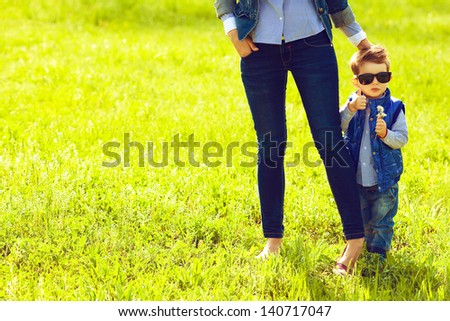 Portrait of fashionable baby boy in trendy sunglasses and his mother standing in the park. Son shows thumb up (ok sign). Sunny spring day. Hipster style. Copy-space. Outdoor shot - stock photo