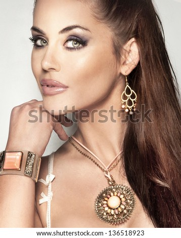 Portrait of fashionable beautiful woman with long brunette hair and amazing jewelry. - stock photo