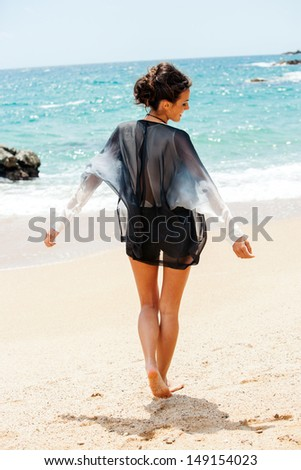 Portrait of fashionable brunette in dark outfit walking on beach. - stock photo