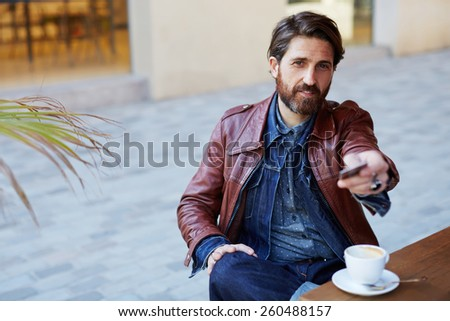 Portrait of fashionable handsome man paying for his coffee with a credit card at the cafe, customer paying at a coffee shop with a credit card - stock photo