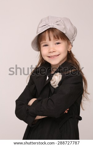 Portrait of fashionable little lady in black coat. Girl in grey hat clasped her hands. - stock photo