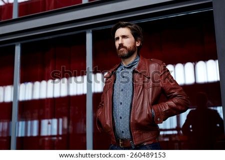Portrait of fashionable mature hipster man dressed in pattern shirt standing indoors with hands in the pockets of leather jacket  - stock photo