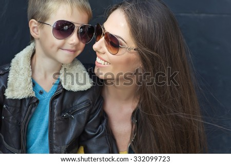 Portrait of fashionable mother hugging her gorgeous baby boy in trendy sunglasses. Family walking in the street. Stylish casual clothes. Sunny  day, blue sky. Outdoor shot - stock photo