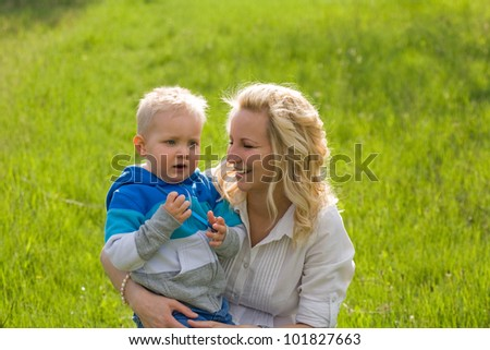 Portrait of fashionable mother with her cute son outdoors in the garden. - stock photo