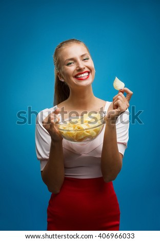 Portrait of fashionable young blond woman in pink-red dress, beautiful lips, bright make-up holding, eating fried potato, fries, chips and posing over blue background. Copy-space. Unhealthy eating - stock photo