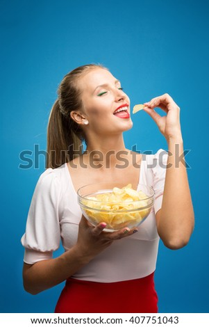 Portrait of fashionable young blond woman in pink-red dress, beautiful lips, bright make-up holding, eating fried potato, fries, chips and posing over blue background. Unhealthy eating. Junk food - stock photo