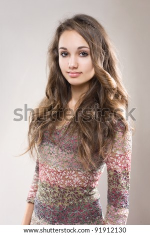 Portrait of fashionable young brunette girl in blue jeans and sweater. - stock photo