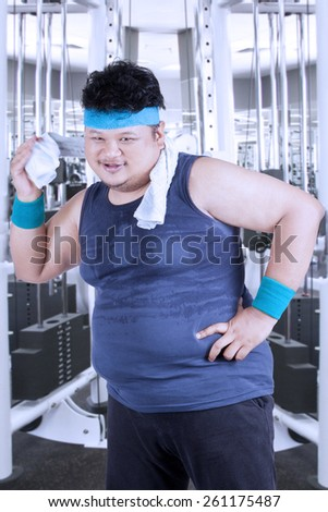 Portrait of fat person with sportswear using a towel to clean his sweat after workout in fitness center - stock photo