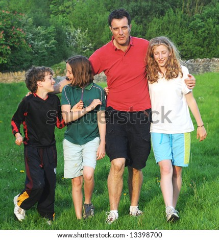 portrait of father and children outdoors - stock photo