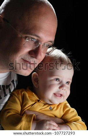 portrait of father and daughter on a black background - stock photo