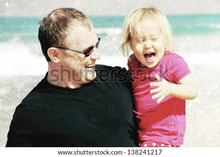 Portrait of father and daughter on the beach. Photo in old image style - stock photo