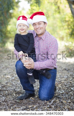 Portrait of Father and Daughter Wearing Santa Hats Outdoors. - stock photo