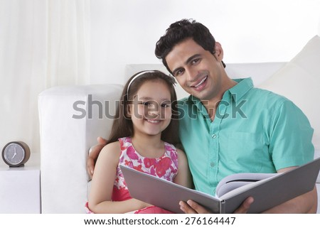 Portrait of father and daughter with file at home - stock photo