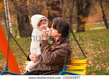 Portrait of father and son in autumn park. Happy dad is holding cute baby boy. Man and (child) kid are smiling, having fun and enjoying nature. Caucasian male model. Autumnal day. Close up, outdoors. - stock photo