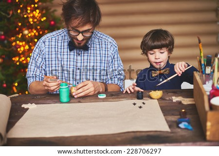 Portrait of father and son preparing Christmas picture at home - stock photo