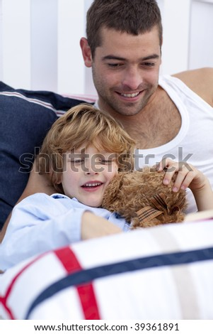 Portrait of father and son reading a book in bed together - stock photo