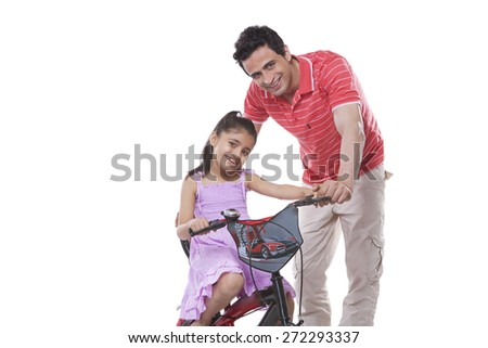 Portrait of father assisting daughter in riding bicycle against white background - stock photo