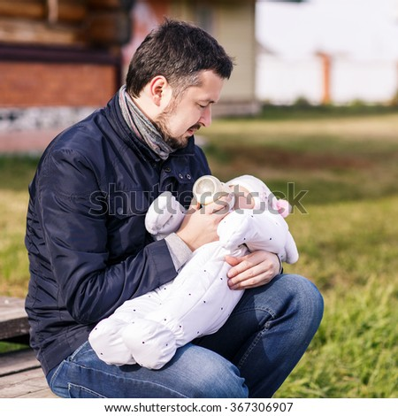Portrait of father feeding newborn baby - stock photo