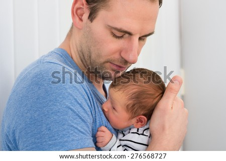 Portrait Of Father Holding Newborn Baby At Home - stock photo