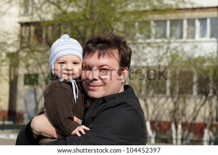 Portrait of father with his son outdoor - stock photo