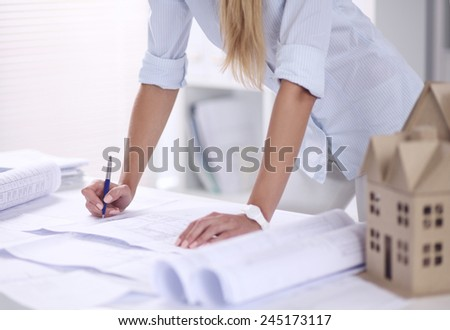 Portrait of female architect with blueprints at desk in office, isolated - stock photo