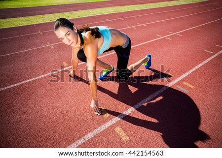 Portrait of female athlete in ready to run position on running track - stock photo