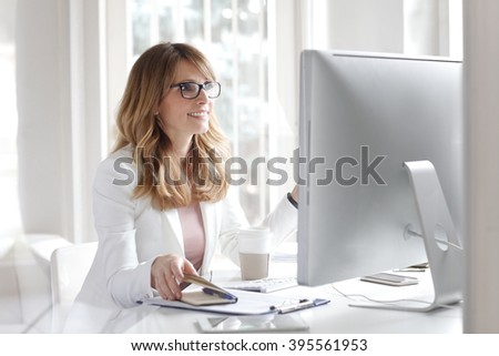 Portrait of female boss working on computer while sitting at office and writing appointments to her diary. - stock photo