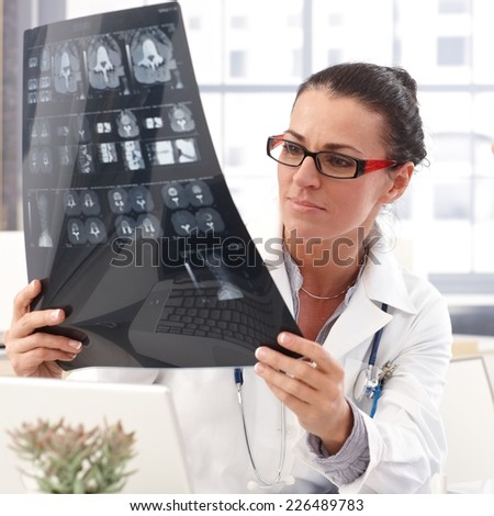 Portrait of female brunette doctor with x-ray image in hand, wearing glasses, stethoscope and lab coat, - stock photo