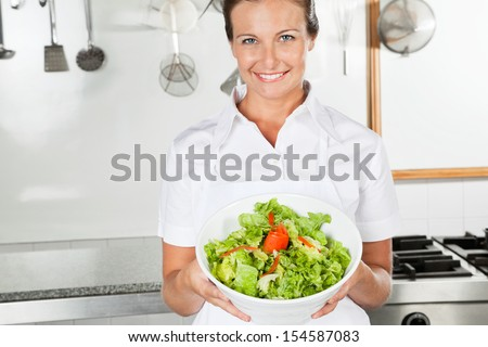 Portrait of female chef presenting bowl of salad in commercial kitchen - stock photo