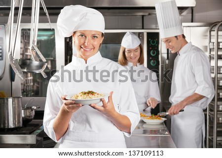 Portrait of female chef presenting dish with colleagues working in industrial kitchen - stock photo