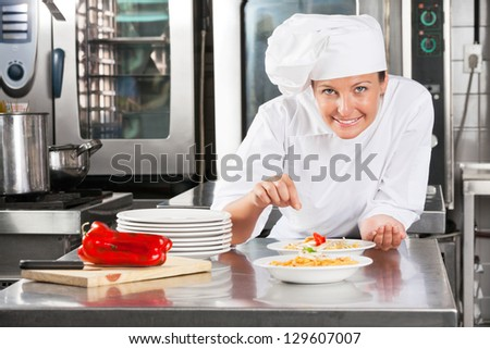 Portrait of female chef sprinkling spices on food at commercial kitchen counter - stock photo