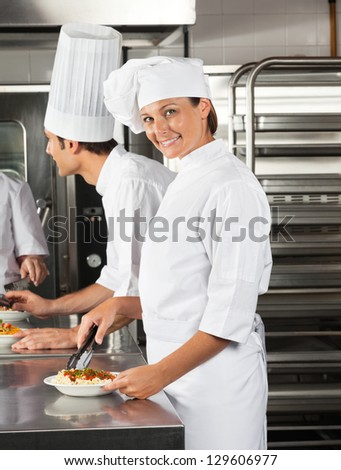 Portrait of female chef with tong and dish in restaurant kitchen - stock photo
