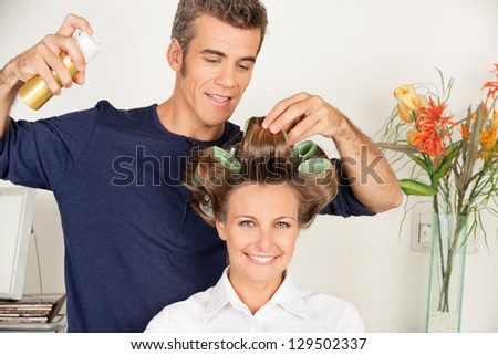 Portrait of female client with hairdresser setting curls with hairspray at salon - stock photo