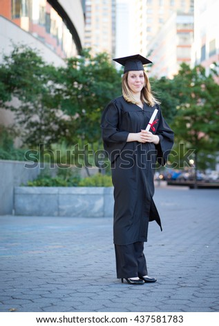 Portrait of female college student in graduation cap and gown holding diploma on campus - stock photo