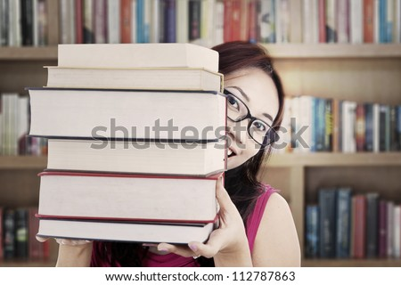 Portrait of female college student smiling behind thick books. shot in the library - stock photo
